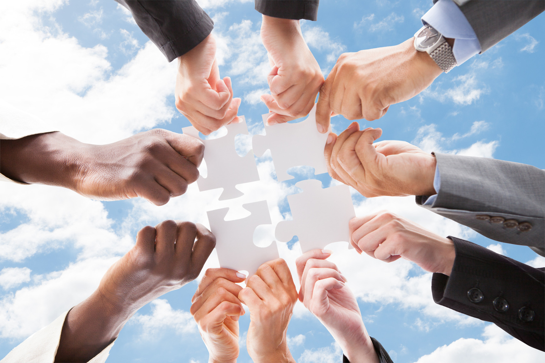 Multiethnic Business People Assembling Jigsaw Puzzle Against Sky